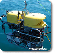 Photo of remotely operated vehicle hanging over the ocean, connected to vessel by an electronic tether