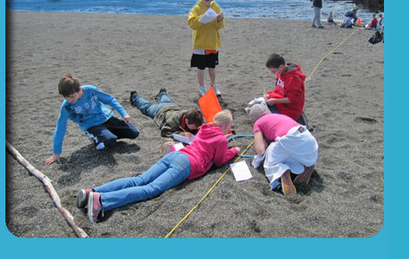 Photo of children taking measurements and learning on the beach.