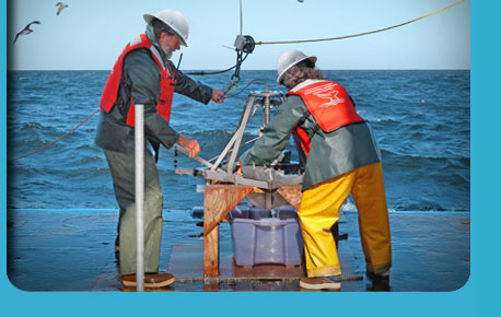 photo of sanctuary scientists on a boat collecting samples from the ocean .
